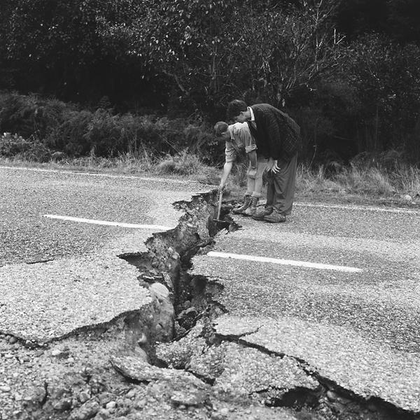 Geologists measure the vertical movement across a rupture created by the earthquake. The side they are standing on has moved downwards relative to the rest of the road. [GNS Science]