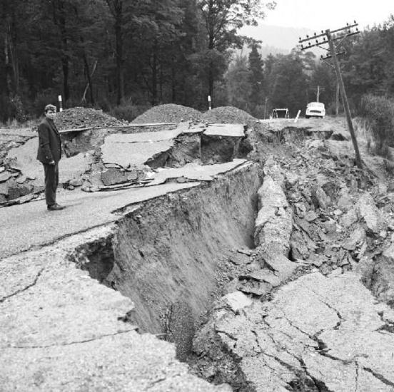 Geologist John Foster stands at the destroyed road, SH6 east of Inangahua. [GNS Science]
