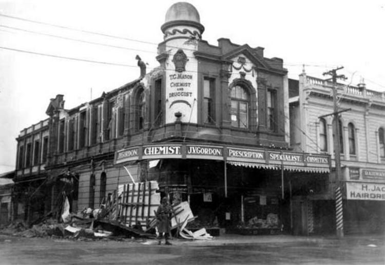 A soldier stands guard outside the heavily damaged chemist's shop operated by J.V. Gordon, on the corner of Queen and Bannister Streets. [Courtesy of Wairarapa Archive]