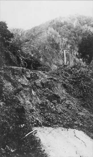 The White Creek Fault scarp, cutting across a road in the Buller Gorge. The scarp, visible as a rocky cliff face, is the result of vertical movement on the fault that displaced the road, leaving one side over 4m higher than the other. [GNS Science]