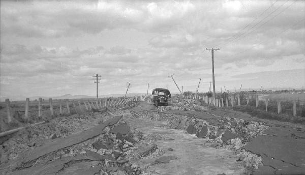 Severe surface damage left this road almost impassable after the 1931 earthquake. Note the dislodged power poles in the background. [GNS Science]