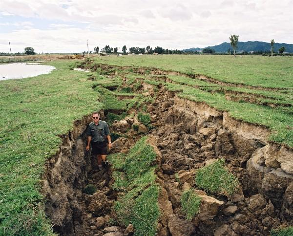 A scientist stands in the spectacular rift that opened in a paddock near East Bank Road during the Edgecumbe earthquake. [GNS Science]