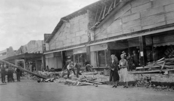 Workers remove debris from Main Street, Pahiatua. The two women in front of the building are Ivy Oates and Irene Oates. 12 March 1934. [Courtesy of Wairarapa Archive]