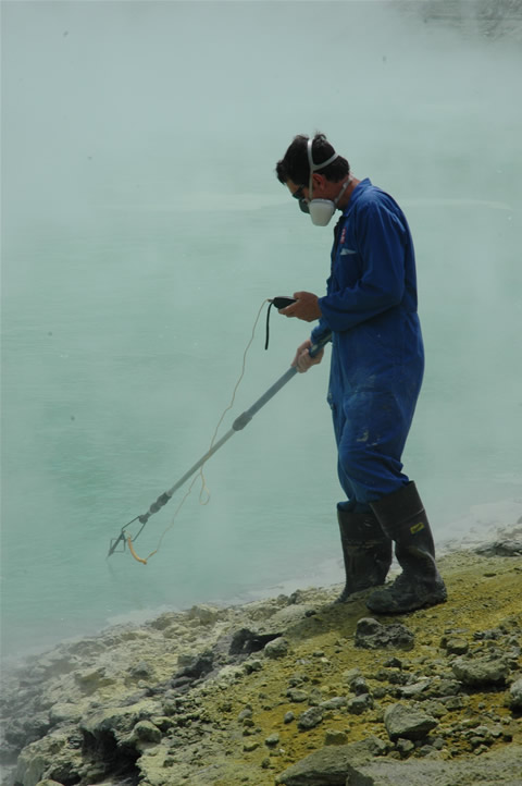 A technician measuring a crater lake temperature.